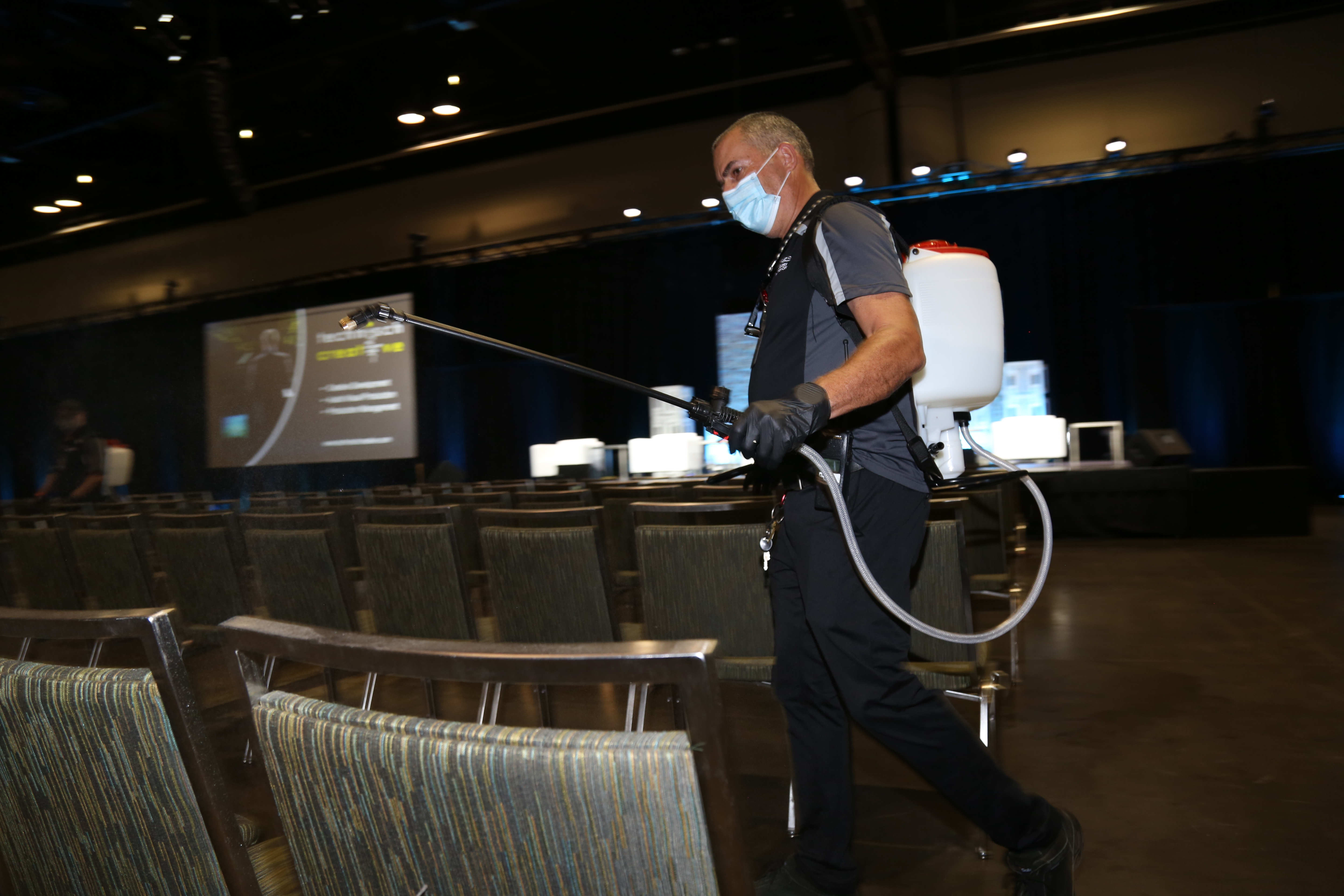 OCCC employee sanitizing the Together Again Expo General Session Area with an electrostatic fogger